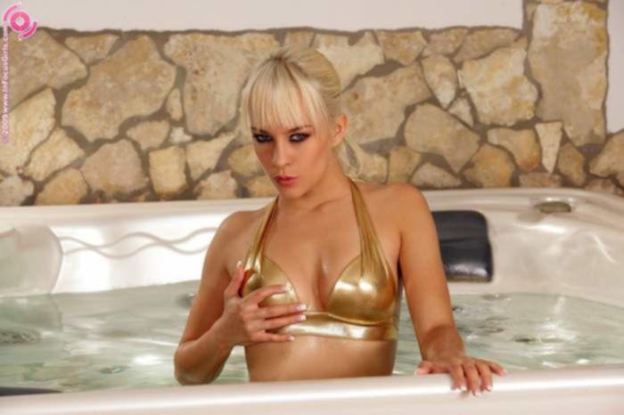 Голая блондинка с большими сиськами, играет в джакузи со своей бритой вагиной