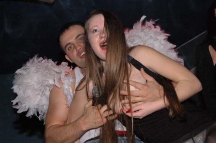 На секс вечеринке ди-джей раздевает рыжую девицу, показывая толпе ее большие сиськи и белые трусики под черными, нейлоновыми колготками